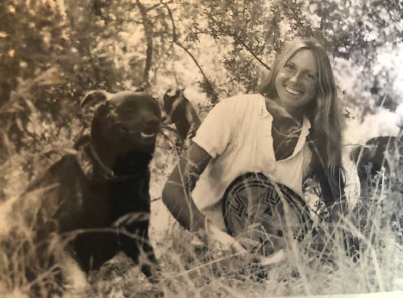 young Christine Adcock in field with black dog
